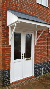 White PVCu door & sidescreen with GRP porch canopy above